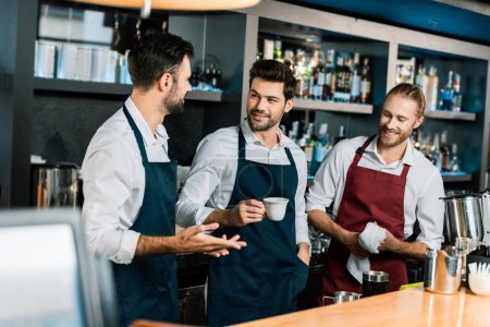 adult barman drinking coffee and speaking with colleagues at workplace