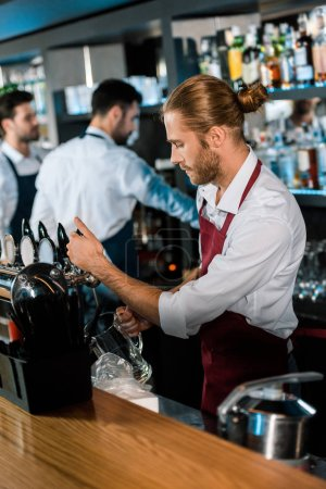 barman in apron pouring beer in glass behind wooden counter at bar
