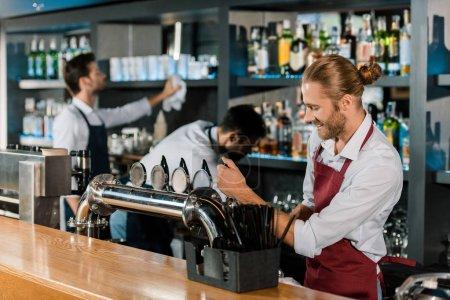 smiling barman pouring beer behind wooden counter at bar
