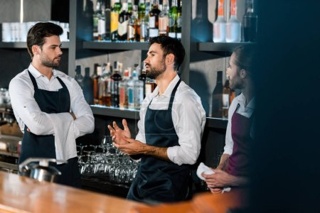 barmen in aprons standing and communicating at workplace
