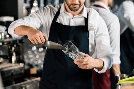 cropped view of  barman in apron putting ice in glass with ice shovel