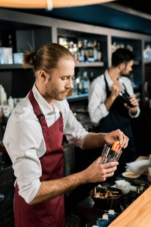 handsome barman decorating glass for cocktail with grapefruit slice