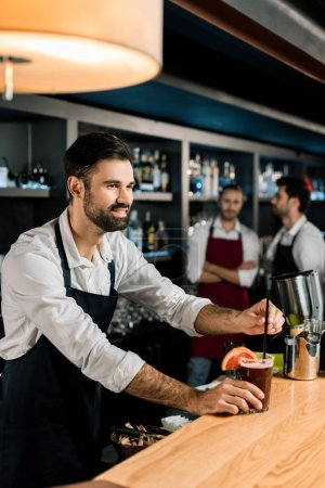 cheerful bartender putting straw in cocktail at wooden counter