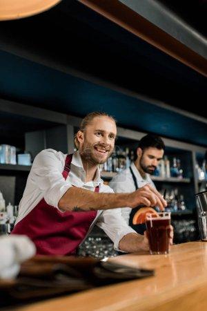 handsome smiling bartender serving cocktail at wooden counter