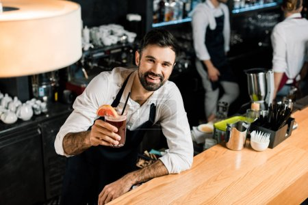 handsome smiling bartender holding cocktail with grapefruit slice and straw