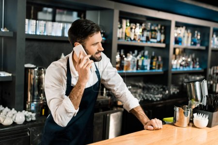 Photo for Barman talking on smartphone and standing in apron in bar - Royalty Free Image
