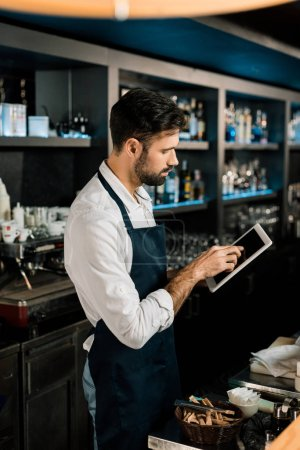 Photo for Barman standing in apron with digital tablet in bar - Royalty Free Image