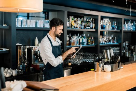 Photo for Barman standing in apron and typing on digital tablet - Royalty Free Image