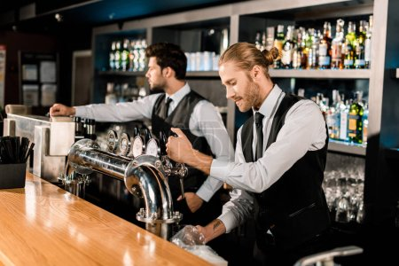 Handsome barman standing and working with coworker in bar