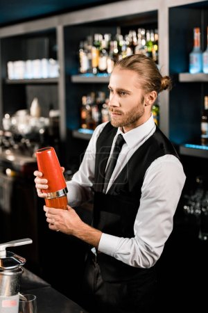 Handsome barman mixing cocktail in shaker