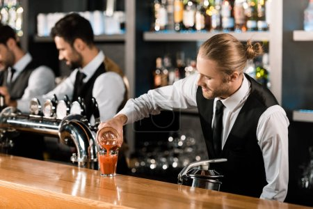 Barman pouring drink in glass on wooden counter