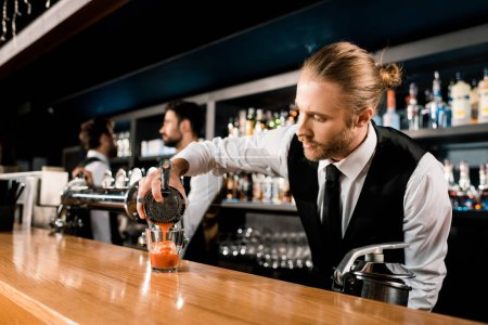 Barman pouring cocktail in glass on bar counter