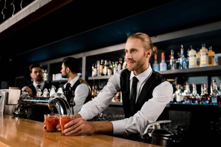 Handsome bartender serving drinks in glasses
