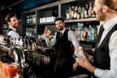 Handsome bartenders standing in bar and smiling