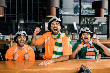 Photo pour Fans de football regarder football jeu et vivats en bar - image libre de droit