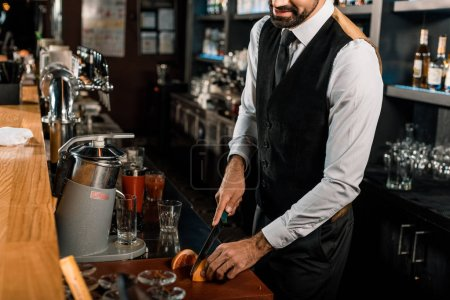 Barman slicing fruit on cutting board in bar