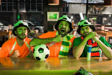 Photo for Football fan screaming and watching game in bar with friends - Royalty Free Image