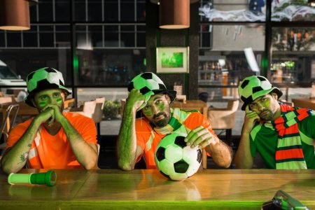 Football fans sitting at bar counter and watching soccer