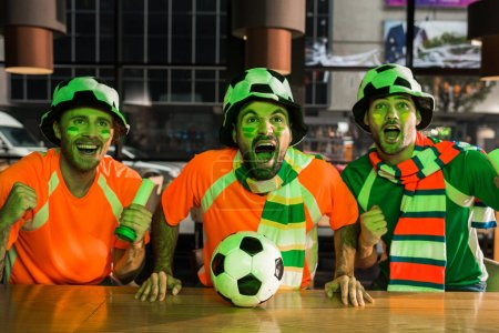 Football fans sitting at bar counter, screaming and watching game