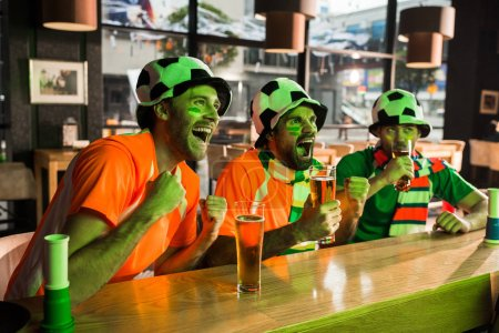 Football fans watching game and cheering in bar