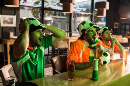 Football fans watching game and screaming in bar