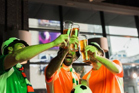 Photo for Football fans clinking glasses with lager and cheering in bar - Royalty Free Image