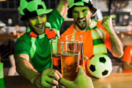 Cheering football fans clinking glasses of beer in bar