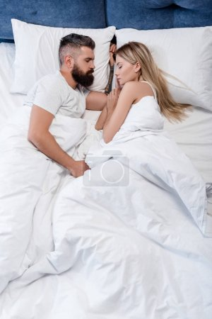 Handsome man and attractive girl sleeping in big white bed in morning
