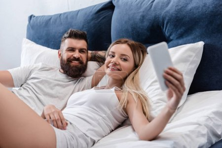 joyful couple posing in bed and taking selfie in morning