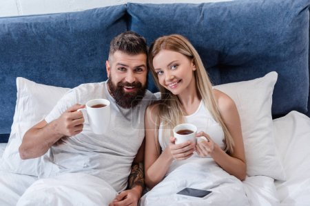 happy couple lying in bed and drinking coffee in morning