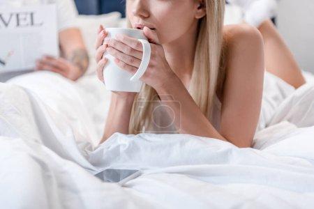 Jeune femme au lit et tenant la tasse à café blanche homme lisant Journal