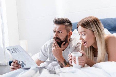L'homme surpris et jeune femme avec coupe couché dans son lit et la lecture des journaux de voyage