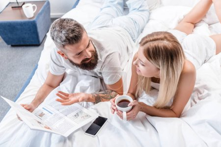 bearded man with newspaper and attractive woman with coffee cup lying in bed and talking