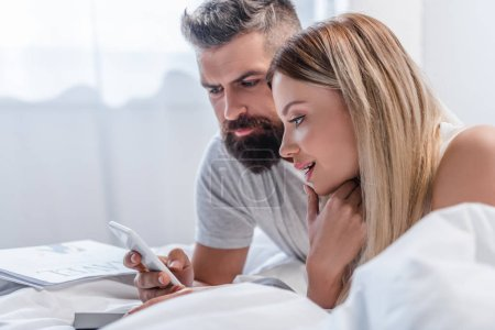 Young couple lying in bed and looking at smartphone screen