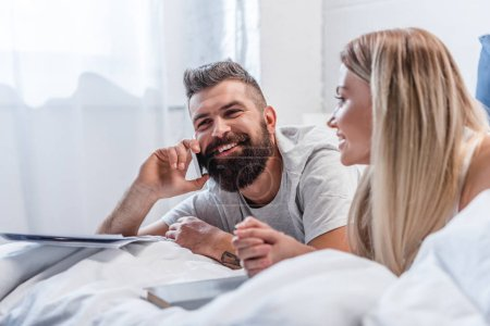 Photo pour Homme barbu parle sur smartphone tout en jeune fille blonde, couché dans son lit - image libre de droit