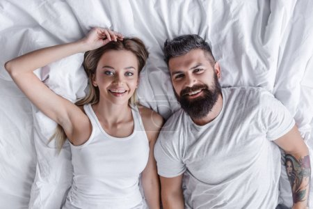 Photo for Pretty couple lying in bed, smiling and looking at camera - Royalty Free Image