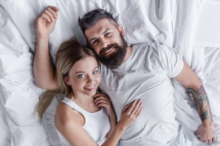 young smiling couple lying in bed and looking at camera