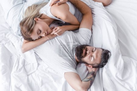 pretty girl putting head on handsome man chest and sleeping in bed