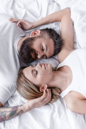 close up view of young couple in love lying head to head and sleeping on white blanket