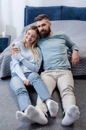 Foto de Hombre guapo sentado en el piso y abrazar la atractiva joven en el dormitorio azul - Imagen libre de derechos