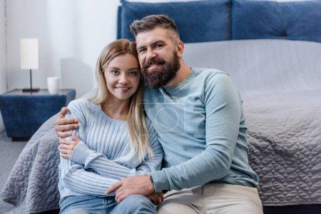 Photo pour Heureux jeune couple assis sur le plancher, souriant et en regardant la caméra dans la chambre bleue - image libre de droit