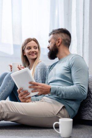 Photo pour Couple souriant et assis dans des vêtements décontractés avec tablette numérique - image libre de droit