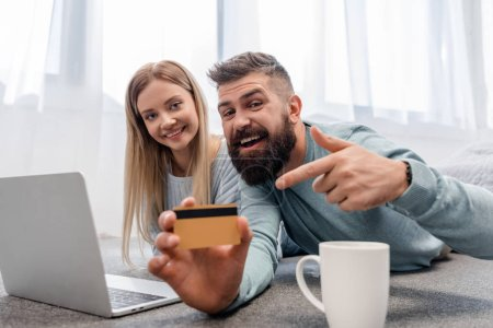 Cheerful couple lying on floor with laptop with credit card