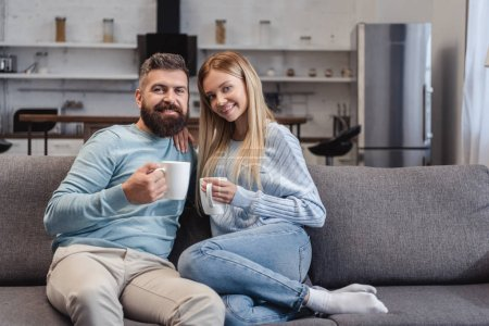 Photo pour Heureux couple assis sur le canapé en vêtements de sport avec boissons - image libre de droit