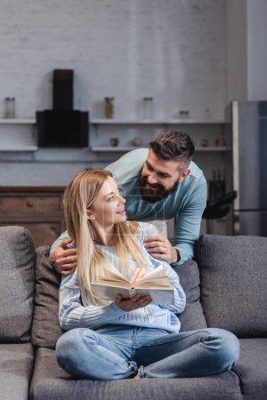 Husband hugging cheerful wife with book