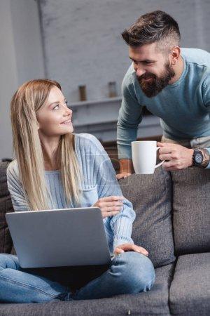 Photo pour Femme assise sur le canapé avec ordinateur portable et mari donnant tasse avec boisson - image libre de droit