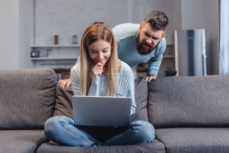 Wife sitting with laptop on sofa and husband looking on monitor