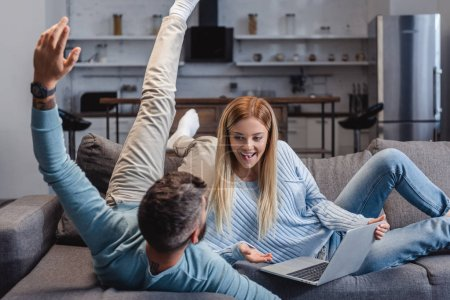Husband and wife relaxing on sofa with laptop