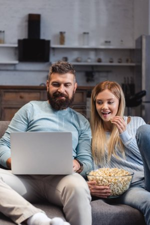 Couple sitting with popcorn and watching movie on laptop