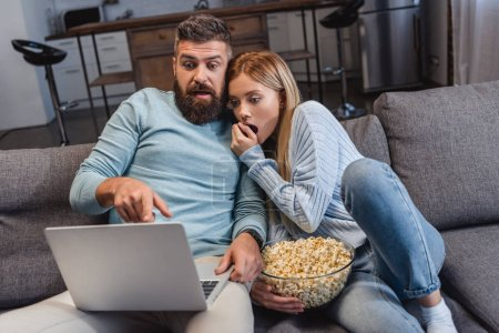 Husband and wife sitting on sofa and watching scary movie on laptop